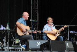 """První, koho jsem letos v Rudolstadtu slyšel: David Bromberg (vpravo; s doprovazečem Markem Cosgrovem), muzikant představovaný jako někdo, kdo má """"ke kořenům americké hudby tak blízko, jako nikdo druhý"""". Nehrál nic autorského (ani hit Mr. Bojangles, se kterým je spojován, nesložil, ale """"jen popularizoval""""), ale předvedl směsku folku (s irskými kořeny), bluegrassu, blues a ragtimu."""