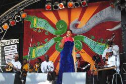 """""""Magickou zemí"""" letošního ročníku byla Tanzánie, jednou z kapel této země (konkrétně z ostrova Zanzibar), kterou jsem slyšel, byla Kithara (v popředí zpěvačka Derya Takkali), spojující, jak praví programová příručka, zvuk klasických taarabských orchestrů s místními tanečními styly, jako je ngoma a kidumbak. Všimněte si nádherného obrazového motivu visícího na scéně. Podobné skvělé nápady byly skoro na všech scénách; na festivalová trička bohužel nepronikly."""