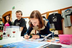 Cédéčka je třeba podepsat. Povšimněte si sklenice vedle Marušky. Má logo Hradeckého slunovratu, (i když to není na fotce vidět) a dobře symbolizuje vášeň pořadatelů pro dobré víno. Proto i tento festival začínal páteční degustací vinařství Moravia víno.