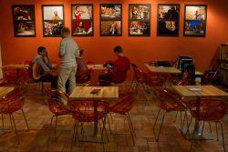 Hlavní stěna v kavárně, ozdobená fotografiemi z místních večerních akcí.