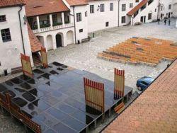 Opuštěné zmoklé podium na nádvoří hradu, kde se měla část programu odehrávat